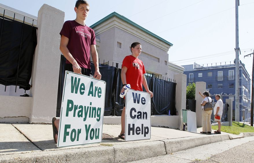 **FILE** Anti-abortion advocates stand outside the Jackson Women's Health Organization in Jackson, Miss., the state's only abortion clinic, on June 27, 2012. (Associated Press)