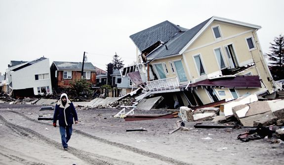 A man walks past destroyed homes on the Rockaway Peninsula in the New York borough of Queens on Tuesday, Nov. 27, 2012. (AP Photo/Seth Wenig)