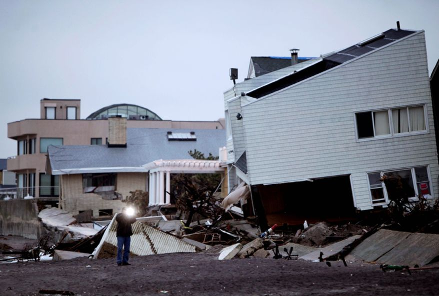A man takes a picture of destroyed homes on the Rockaway Peninsula in the New York borough of Queens on Tuesday, Nov. 27, 2012. New York Gov. Andrew Cuomo wants huge electrical transformers hauled to upper floors of commercial buildings and the ability to shutter subways as part of a $9 billion plan to protect New York City from the next superstorm. Mr. Cuomo said that the government must take preventive measures now to avoid future loss of life and billions more in damage. (AP Photo/Seth Wenig)
