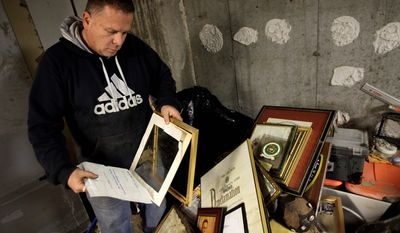 Bill Acosta sorts through his numerous diplomas, awards and other important documents in his basement office on the Rockaway Peninsula in the New York borough of Queens on Tuesday, Nov. 27, 2012. Mr. Acosta, who is a veteran with a long record of government service, is upset that the Federal Emergency Management Agency or any other government office was unable to offer him financial assistance. (AP Photo/Seth Wenig)