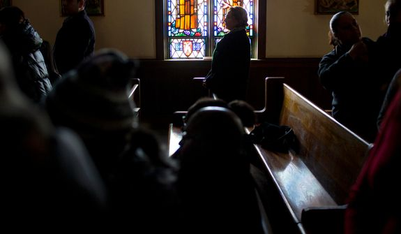 Without lights or heat, parishioners take part in a Sunday service at St. Camillus Roman Catholic Church in the Rockaway Park neighborhood of the borough of Queens, New York, Sunday, Nov.11, 2012, almost two weeks in the wake of Superstorm Sandy. (AP Photo/Craig Ruttle)