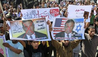 "** FILE ** In this Friday, Sept. 14, 2012, file photo, Palestinian Islamic Jihad supporters rally with banners depicting Morris Sadek during a protest in Khan Younis, southern Gaza Strip, as part of widespread anger across the Muslim world about a film ridiculing Islam's Prophet Muhammad. The banners in Arabic read, ""Death to Israel,"" ""Death to America"" and ""Anyone but God's Prophet."" (AP Photo/Adel Hana, File)"