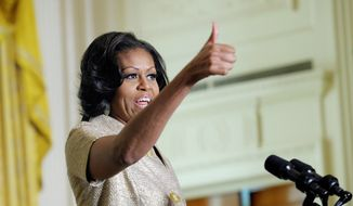 First lady Michelle Obama gives a thumbs up to those who decorated the White House as she speaks to military families in the East Room of the White House in Washington, Wednesday, Nov. 28, 2012. The theme for the White House Christmas 2012 is Joy to All.  (AP Photo/Susan Walsh)
