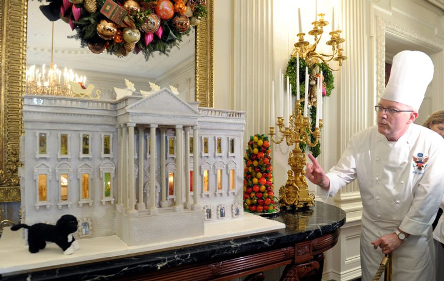 White House Pastry Chef Bill Yosses explains his design for the nearly 300-pound gingerbread house of the White House, on display in the State Dining Room of the White House in Washington, Wednesday, Nov. 28, 2012. The house features Bo, the Obama family dog, left,  a vegetable garden and views inside the White House. (AP Photo/Susan Walsh)