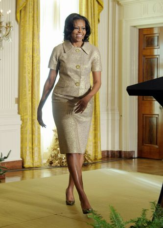First lady Michelle Obama walks up to the microphone to speaks in the East Room of the White House in Washington, Wednesday, Nov. 28, 2012, to welcome military families during a preview of the White House holiday decorations. The theme for the White House Christmas 2012 is Joy to All. (AP Photo/Susan Walsh)