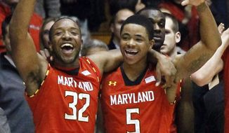 Maryland's Dezmine Wells (32) and Nick Faust celebrate their 77-57 win over Northwestern late in the second half of an NCAA college basketball game, Tuesday, Nov. 27, 2012, in Evanston, Ill. (AP Photo/Charles Rex Arbogast)