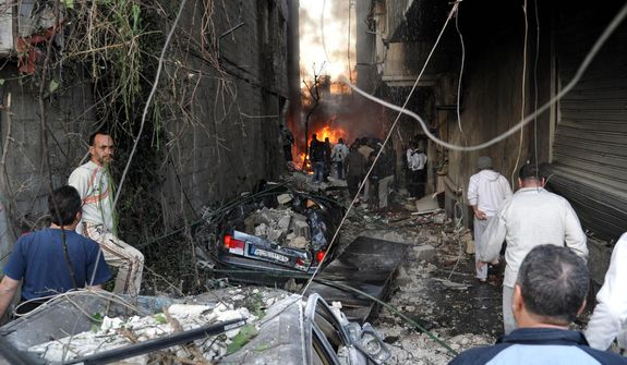 In this photo released by the Syrian official news agency SANA, Syrians gather at an alley destroyed by two cars bombs in the Jaramana neighborhood of Damascus, Syria, on Wednesday, Nov. 28, 2012. (AP Photo/SANA)