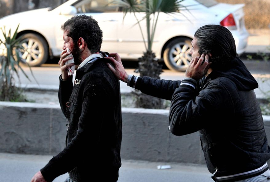 In this photo released by the Syrian official news agency SANA, a man helps another man who was injured after two cars bombs exploded in the Jaramana neighborhood of Damascus, Syria, on Wednesday, Nov. 28, 2012. (AP Photo/SANA)