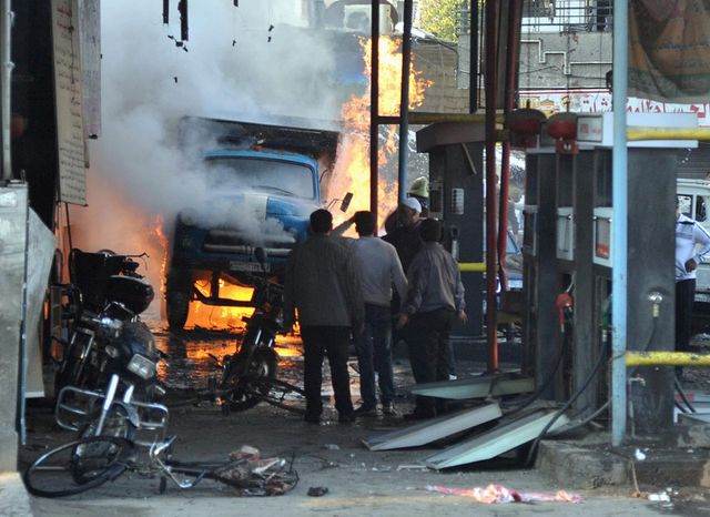In this photo released by the Syrian official news agency SANA, Syrian citizens stand near a burning truck that was destroyed by two cars bombs, at Jaramana neighborhood, in the suburb of Damascus, Syria, Wednesday, Nov. 28, 2012. (AP Photo/SANA)