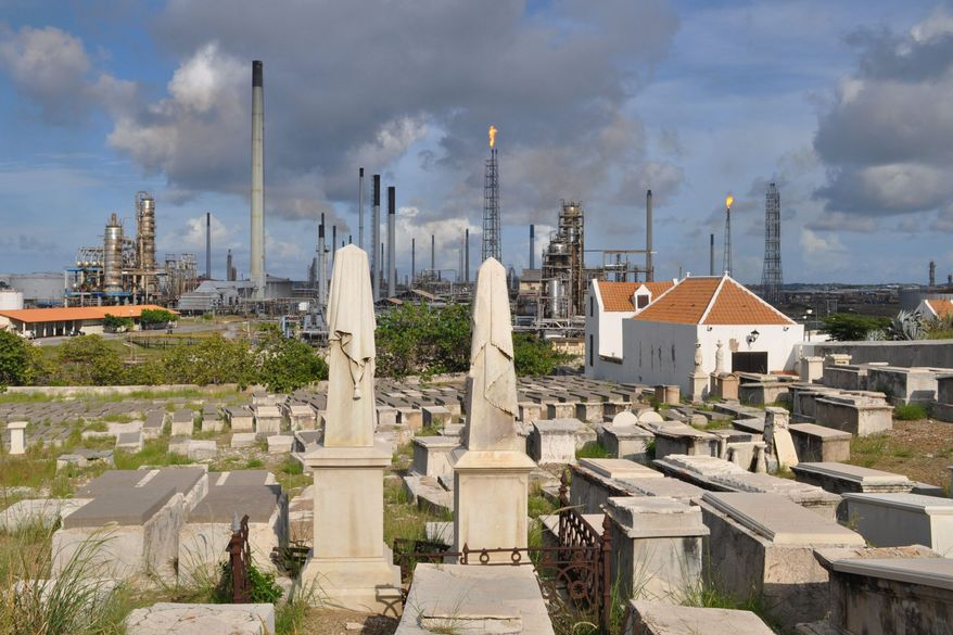 A portion of the Beth Haim cemetery, backdropped by the Isla oil refinery, is seen in Blenheim, on the outskirts of Willemstad, Curacao. (Associated Press)