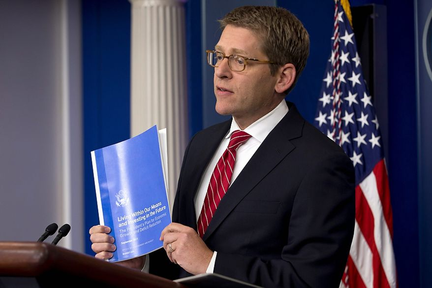 White House press secretary Jay Carney holds up a copy of the President's Plan for Economic Growth and Deficit Reduction during his daily news briefing at the White House in Washington on Thursday, Nov. 29, 2012, as President Obama was having a private lunch with former Republican presidential candidate Mitt Romney. (AP Photo/Jacquelyn Martin)