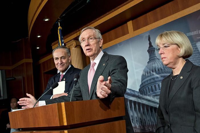 """Senate Majority Leader Harry Reid (center), flanked by Sen. Charles E. Schumer (left) and Sen. Patty Murray, gestures during a news conference on Capitol Hill in Washington on Thursday, Nov. 29, 2012, following a meeting with Treasury Secretary Timothy F. Geithner on the """"fiscal cliff"""" negotiations. """"We're still waiting for a serious offer from Republicans,"""" Mr. Reid said. (AP Photo/J. Scott Applewhite)"""