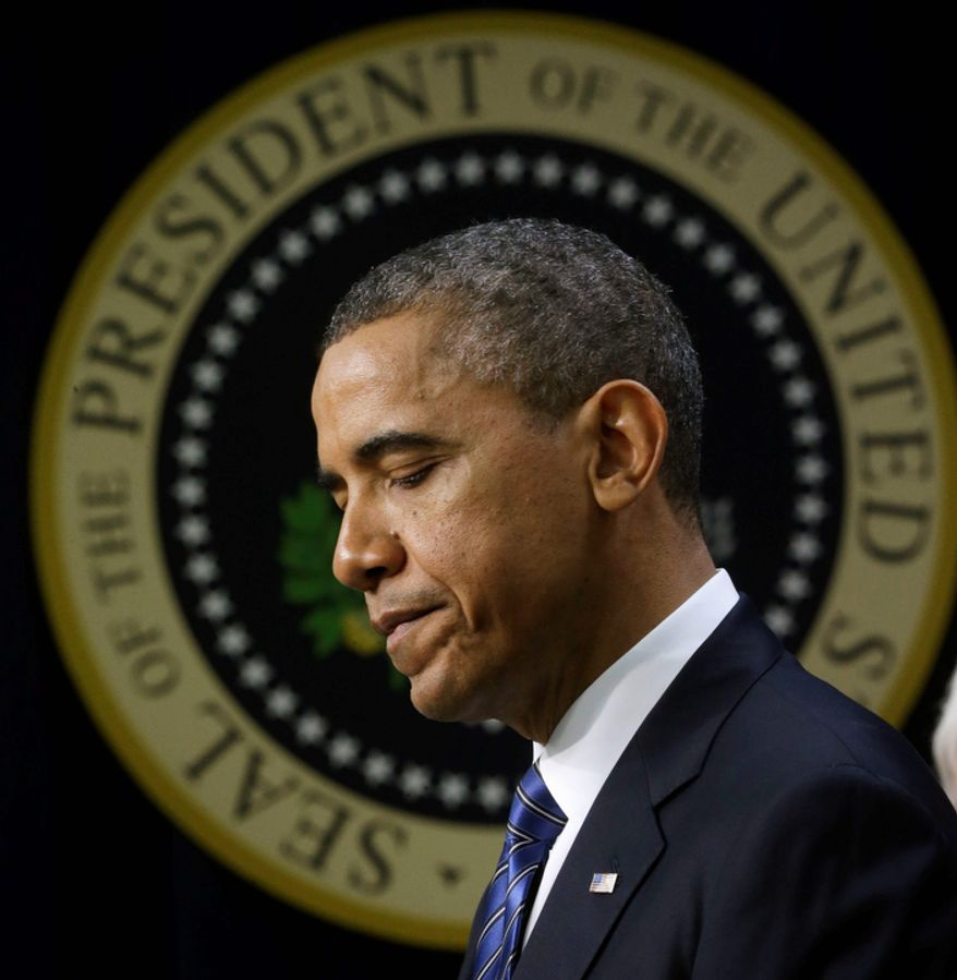 With the presidential seal in the background, President Obama pauses in the Eisenhower Executive Office Building on the White House campus in Washington on Wednesday, Nov. 28, 2012, where he spoke about how middle-class Americans would see their taxes go up if Congress fails to act to extend tax cuts. (AP Photo/Pablo Martinez Monsivais)