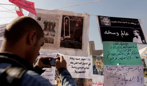An Egyptian protester photographs newspapers and placards on display in a makeshift museum in Tahrir Square in Cairo on Thursday, Nov. 29, 2012. Members of an Islamist-dominated panel tasked with writing Egypt's new constitution are gathering to vote on the document's final draft. (AP Photo/Maya Alleruzzo)
