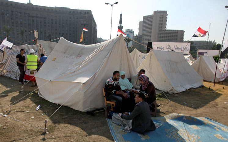 Egyptian protesters sit next to tents in Tahrir Square in Cairo on Wednesday, Nov. 28, 2012. (AP Photo/Khalil Hamra)
