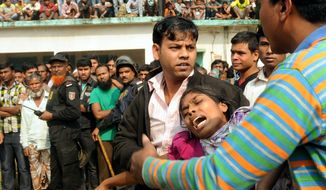 ** FILE ** People console a woman whose relative was killed in a fire at a garment factory outside Dhaka, Bangladesh, Sunday, Nov. 25, 2012. At least 112 people were killed late Saturday night in a fire that raced through the multi-story garment factory just outside of Bangladesh's capital, an official said Sunday. (AP Photo/Hasan Raza)