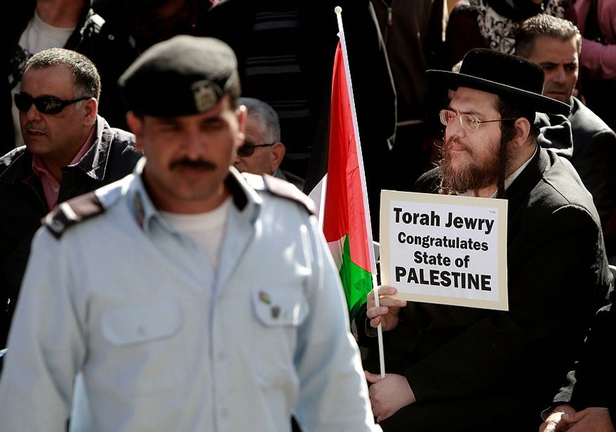 A Hassidic Jew holds a Palestinian flag and a sign during a rally supporting the Palestinian UN bid for observer state status, in the West bank city of Ramallah, Thursday, Nov. 29, 2012. The Palestinians are certain to win U.N. recognition as a state on Thursday but success could exact a high price: delaying an independent state of Palestine because of Israel's vehement opposition. (AP Photo/Majdi Mohammed)