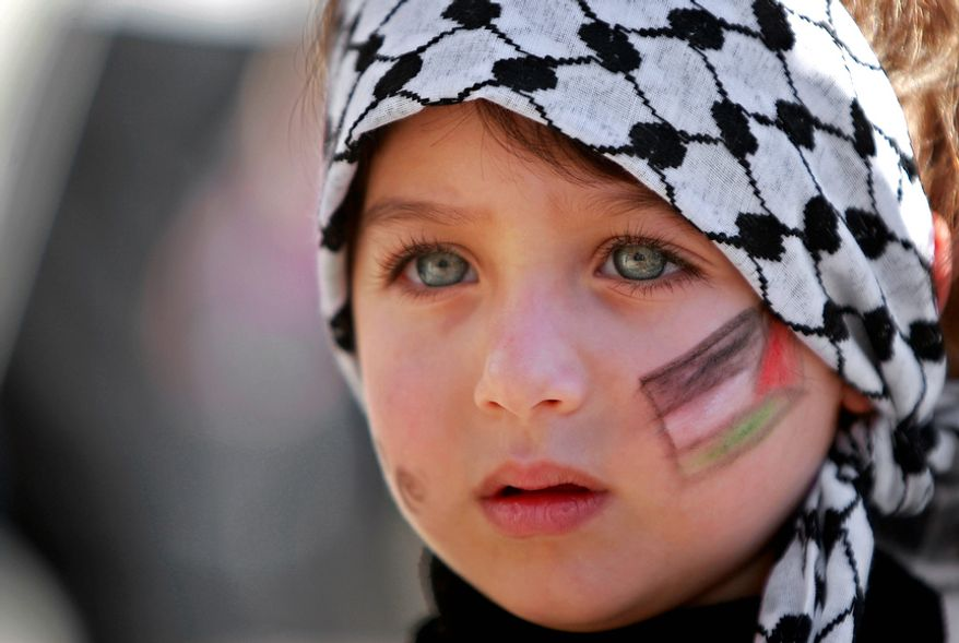 A girl with the Palestinian flag painted  on her face attends a rally supporting the Palestinian UN bid for observer state status, in the West bank city of Ramallah, Thursday, Nov. 29, 2012. The Palestinians are certain to win U.N. recognition as a state on Thursday but success could exact a high price: delaying an independent state of Palestine because of Israel's vehement opposition. (AP Photo/Majdi Mohammed)