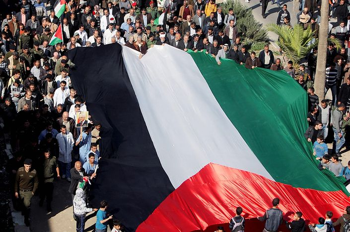 People hold a giant Palestinian flag during a rally in support of the Palestinian UN bid for observer state status, in the West Bank town of Jenin, Thursday, Nov. 29, 2012. The Palestinians are certain to win U.N. recognition as a state on Thursday but success could exact a high price: delaying an independent state of Palestine because of Israel's vehement opposition. (AP Photo/Mohammed Ballas)