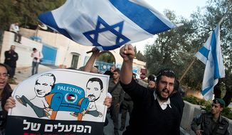 "Israeli right wing activists demonstrate against the Palestinian U.N. bid for observer state status, in front of the U.N. headquarters in Jerusalem, Thursday, Nov. 29, 2012. The Palestinians are certain to win U.N. recognition as a state on Thursday but success could exact a high price: delaying an independent state of Palestine because of Israel's vehement opposition. Hebrew on sign reads: ""Abu Mazen's workers."" (AP Photo/Sebastian Scheiner)"