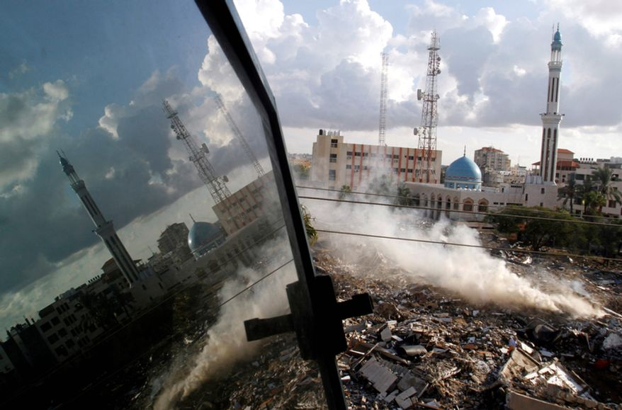 Smoke rises on Friday, Nov. 23, 2012, from the Hamas government building known as Abu Khadra, which was destroyed in an Israeli airstrike two days before in Gaza City, Gaza Strip. (AP Photo/Hatem Moussa)