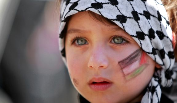 A girl with the Palestinian flag painted on her face attends a rally supporting the Palestinian U.N. bid for observer state status, in the West Bank city of Ramallah on Thursday, Nov. 29, 2012. The Palestinians are certain to win U.N. recognition as a state on Thursday, but success could exact a high price: delaying an independent state of Palestine because of Israel's vehement opposition. (AP Photo/Majdi Mohammed)
