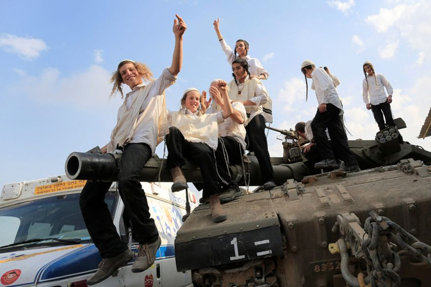 Ultra-Orthodox Jews of the Bratslav Hasidic sect who gathered to show support for Israeli forces, dance atop a tank in southern Israel, close to the Israel-Gaza Strip border, on Thursday, Nov. 22, 2012. A cease-fire agreement between Israel and the Gaza Strip's Hamas rulers took effect Wednesday night, bringing an end to eight days of the fiercest fighting in years and possibly signaling a new era of relations between the bitter enemies. (AP Photo/Tsafrir Abayov)