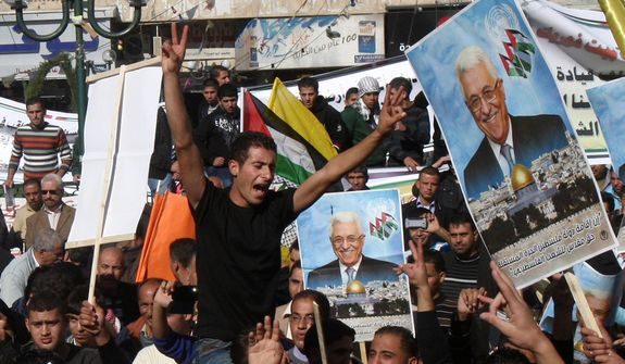 Palestinians hold pictures of President Mahmoud Abbas and wave flags during a rally supporting the Palestinian U.N. bid for observer state status, in the West Bank city of Nablus on Thursday, Nov. 29, 2012. (AP Photo/Nasser Ishtayeh)