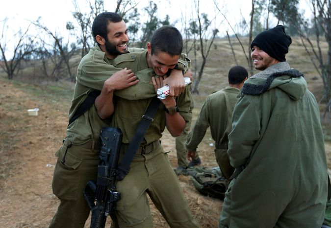 An Israeli soldier (left) hugs a comrade (center) to congratulate him for his birthday at a staging area near the Israel-Gaza Strip border in southern Israel on Thursday, Nov. 22, 2012. A cease-fire agreement between Israel and the Gaza Strip's Hamas rulers took effect Wednesday night, bringing an end to eight days of the fiercest fighting in years. (AP Photo/Lefteris Pitarakis)