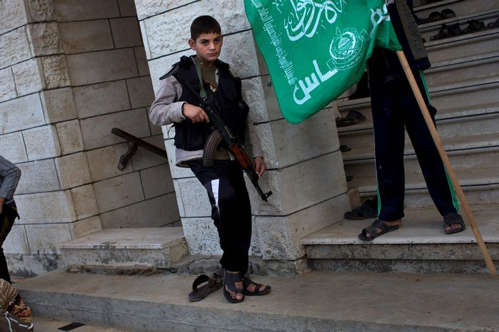 A Palestinian child holds a Kalashnikov weapon from a Hamas member (not pictured) during the funeral of Hamas member Joudeh Shamallah in Gaza City, Gaza Strip, on Saturday, Nov. 24, 2012. According to family members, Shamallah was badly injured during the latest Israeli-Hamas fight and died from wounds Saturday. (AP Photo/Bernat Armangue)