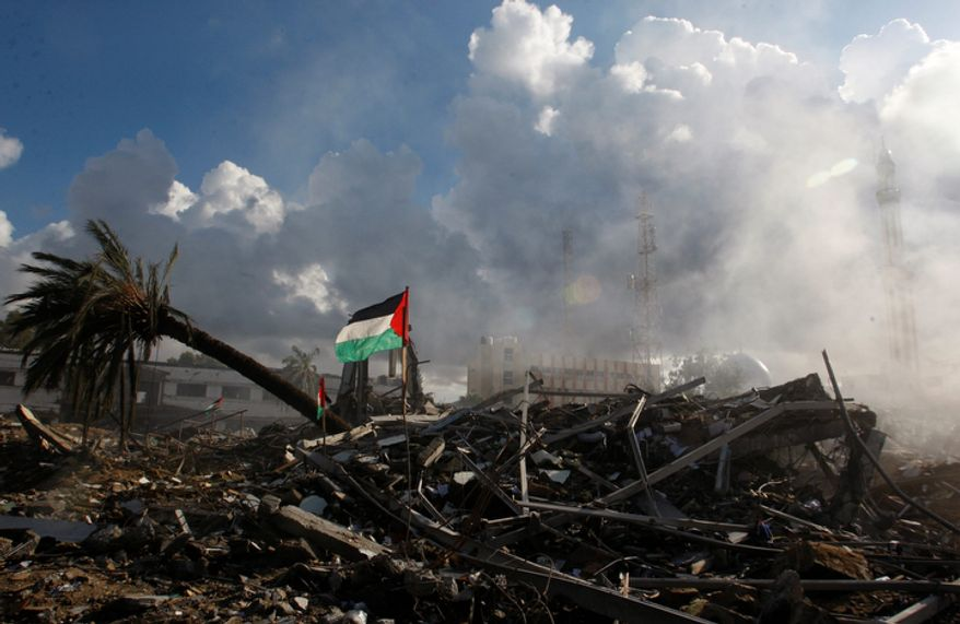 Smoke rises on Friday, Nov. 23, 2012, from the Hamas government building known as Abu Khadra, which was destroyed in an Israeli airstrike two days earlier in Gaza City, Gaza Strip. In Israel, a poll showed that about half of Israelis think their government should have continued its military offensive against Hamas. (AP Photo/Hatem Moussa)