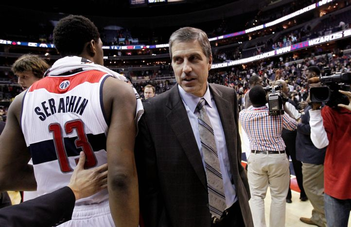 Washington Wizards coach Randy Wittman comes off the court as forward Kevin Seraphin (13) heads to an interview after an NBA basketball game against the Portland Trail Blazers on Wednesday, Nov. 28, 2012, in Washington. The Wizards won for the first time this season after 12 losses, 84-82. (AP Photo/Alex Brandon)