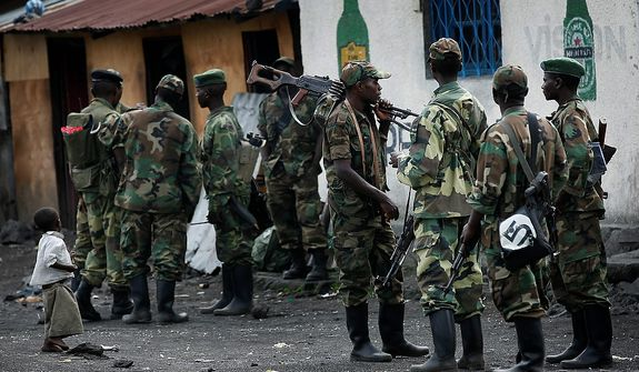 M23 rebels gather  in the eastern Congo town of Sake, some 27 kms west of Goma, Thursday Nov. 29, 2012. Rebels, who last week seized one of the most important cities in eastern Congo and advanced beyond, said Thursday that they had pulled back several miles (kilometers ) to the town of Sake and were on track to leave the key city of Goma by Friday, in accordance with a deadline imposed by the international community.(AP Photo/Jerome Delay)