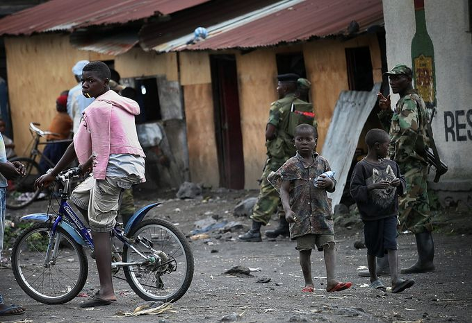 Children walk past M23 rebels in the eastern Congo town of Sake, some 27 kms west of Goma, Thursday Nov. 29, 2012. Rebels, who last week seized one of the most important cities in eastern Congo and advanced beyond, said Thursday that they had pulled back several miles (kilometers ) to the town of Sake and were on track to leave the key city of Goma by Friday, in accordance with a deadline imposed by the international community.(AP Photo/Jerome Delay)