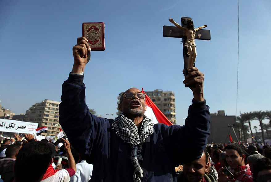 "An Egyptian protesters holds a cross and a Quran as he chants anti-Muslim Brotherhood slogans at an opposition rally in Tahrir Square, in Cairo, Egypt, Friday, Nov. 30, 2012. Egypt's opposition has called for a major rally Friday in Cairo's Tahrir Square, where some demonstrators have camped out in tents since last week to protest decrees that President Mohammed Morsi issued to grant himself sweeping powers. Hundreds gathered in the plaza for traditional Friday prayers, then broke into chants of ""The people want to bring down the regime!"" ó echoing the refrain of the Arab Spring revolts, but this time against a democratically elected leader. Other cities around Egypt braced for similar protests. (AP Photo/Khalil Hamra)"