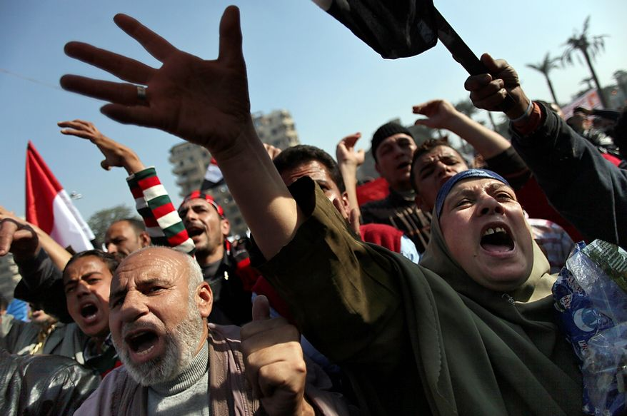 """Egyptian protesters chant anti-Muslim Brotherhood slogans as they attend a rally in Tahrir Square, in Cairo, Egypt, Friday, Nov. 30, 2012. Egypt's opposition has called for a major rally Friday in Cairo's Tahrir Square, where some demonstrators have camped out in tents since last week to protest decrees that President Mohammed Morsi issued to grant himself sweeping powers. Hundreds gathered in the plaza for traditional Friday prayers, then broke into chants of """"The people want to bring down the regime!"""" ó echoing the refrain of the Arab Spring revolts, but this time against a democratically elected leader. Other cities around Egypt braced for similar protests.(AP Photo/Khalil Hamra)"""