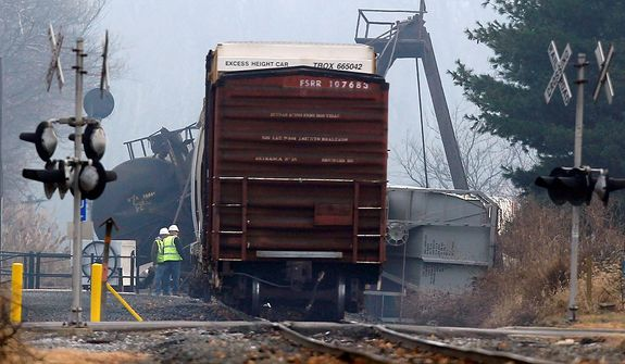 Officials stand next to derailed freight train cars in Paulsboro, N.J., Friday, Nov. 30, 2012. People in three southern New Jersey towns were told Friday to stay inside after a freight train derailed and several tanker cars carrying hazardous materials toppled from a bridge and into a creek. At least one tanker car may contain vinyl chloride, Gloucester County Emergency Management director J. Thomas Butts told WPVI-TV. (AP Photo/Mel Evans)