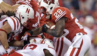 Wisconsin running back Montee Ball (28) is tackled by Nebraska safety P.J. Smith (13) during the first half of the Big Ten championship NCAA college football game Saturday, Dec. 1, 2012, in Indianapolis. (AP Photo/Michael Conroy)