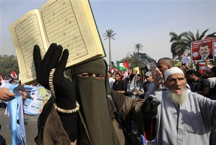 A supporter of Egyptian President Mohammed Morsi holds a Koran and a poster of the president at a rally in front of Cairo University in Cairo, Egypt, Saturday, Dec. 1, 2012. (AP Photo/Thomas Hartwell)