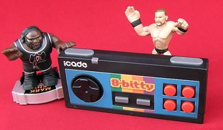 Mark Henry and Randy Orton from Mattel's Apptivity WWE Rumblers admire Think Geek's iCade 8-Bitty controller. (Photo by Joseph Szadkowski/The Washington Times)