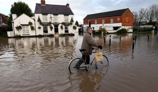 The waters in Tewkesbury turn a bicyclist into a pedestrian. Rain and winds battered areas of Britain in late November, flooding 800 homes, officials said. With more storms on the way, the government and the insurance industry are engaged in finger-pointing about who should pay. (Associated Press)