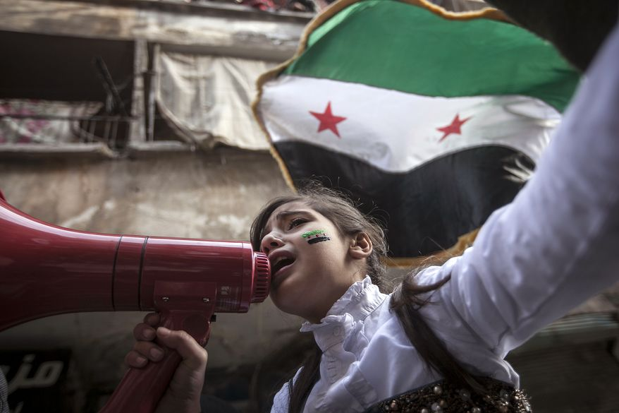 A Syrian girl chants slogans during a demonstration after prayers in the Bustan Al-Qasr district of Aleppo, Syria, on Friday, Nov. 30, 2012. (AP Photo/Narciso Contreras)