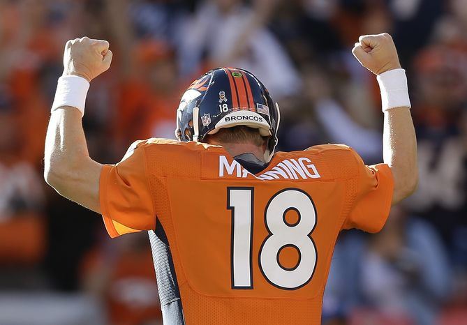 Denver Broncos quarterback Peyton Manning (18) reacts after throwing a touchdown pass to Denver Broncos defensive tackle Mitch Unrein (96) against the Tampa Bay Buccaneers in the first quarter of an NFL football game, Sunday, Dec. 2, 2012, in Denver. (AP Photo/Joe Mahoney)