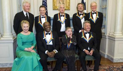 Ballerina Natalia Makarova (front row, second from right) reacts to all the photos being taken during a group photo for the Kennedy Center Honoress after a State Department dinner on Saturday, Dec. 1, 2012, in Washington. From left are former President Bill Clinton, Secretary of State Hillary Rodham Clinton, John Paul Johns, Buddy Guy, Jimmy Page, Miss Makarova, Robert Plant, Dustin Hoffman and David Letterman. (AP Photo/Kevin Wolf)