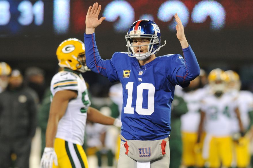 New York Giants quarterback Eli Manning (10) signals a touchdown during the second half of an NFL football game Sunday, Nov. 25, 2012 in East Rutherford, N.J. After further review Manning's pass to Hakeem Nicks was ruled a touchdown. (AP Photo/Bill Kostroun)