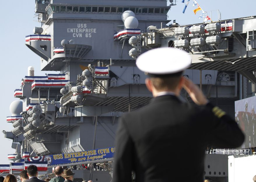 A Navy officer salutes during the inactivation ceremony for the USS Enterprise, the first nuclear-powered aircraft carrier, at Naval Station Norfolk on Saturday, Dec. 1, 2012, in Norfolk, Va. The ship served in the fleet for 51 years. (AP Photo/Steve Helber)
