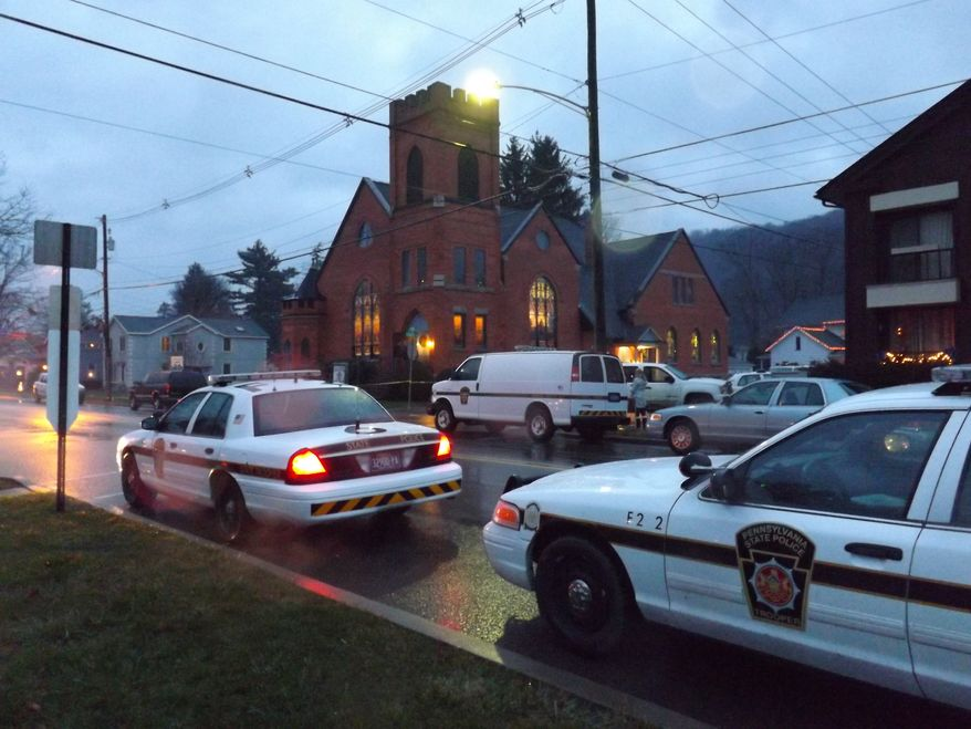 Police cars sit outside the 180-year-old First United Presbyterian Church of Coudersport on Dec. 2, 2012, after church organist Darlene Sitler, 53, was shot to death by her ex-husband Gregory Eldred, 52, during a worship service. (Associated Press/The Bradford Era)