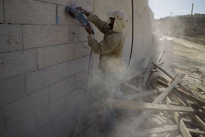 A Palestinian man works Dec. 2, 2012, at a new housing development in the Jewish West Bank settlement of Maaleh Adumim, near Jerusalem. (Associated Press)