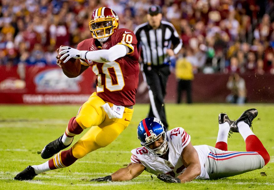Washington Redskins quarterback Robert Griffin III (10) scrambles for a 12 yard gain before fumbling the ball in the first quarter as the Washington Redskins play the New York Giants for monday night football at FedEx Field, Landover, Md., Monday, December 3, 2012. The ball was recovered by Washington Redskins wide receiver Josh Morgan (15) who ran the ball in for a 13 yard touchdown to put the Redskins up 7-3. (Andrew Harnik/The Washington Times)
