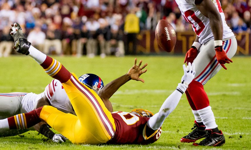 Washington Redskins quarterback Robert Griffin III (10) fumbles after scrambling for a 12 yard gain in the first quarter as the Washington Redskins play the New York Giants for monday night football at FedEx Field, Landover, Md., Monday, December 3, 2012. The ball was recovered by Washington Redskins wide receiver Josh Morgan (15) who ran the ball in for a 13 yard touchdown to put the Redskins up 7-3. (Andrew Harnik/The Washington Times)